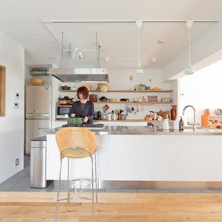 大阪の北欧スタイルのおしゃれなキッチン (オープンシェルフ、白いキャビネット、ステンレスカウンター、白いキッチンパネル、シルバーの調理設備、無垢フローリング、茶色い床、グレーのキッチンカウンター) の写真