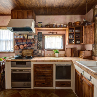 Country l-shaped kitchen in Other with a double-bowl sink, recessed-panel cabinets, distressed cabinets, tile benchtops, brown floor and orange benchtop.