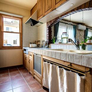 他の地域の地中海スタイルのおしゃれなキッチン (ドロップインシンク、落し込みパネル扉のキャビネット、中間色木目調キャビネット、テラコッタタイルの床、茶色い床) の写真