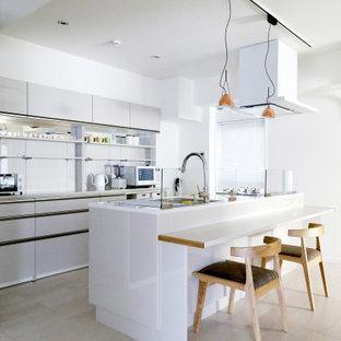 東京23区のコンテンポラリースタイルのおしゃれなアイランドキッチン (フラットパネル扉のキャビネット、グレーのキャビネット、グレーのキッチンパネル、淡色無垢フローリング、ベージュの床、グレーのキッチンカウンター) の写真