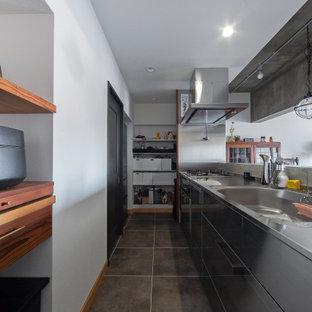 Diseño de cocina lineal, moderna, pequeña, abierta, con fregadero bajoencimera, armarios con rebordes decorativos, encimera de acero inoxidable, salpicadero blanco, suelo de baldosas de cerámica, una isla, suelo gris y papel pintado