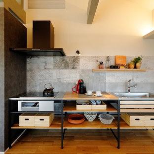 他の地域のモダンスタイルのおしゃれなキッチン (シングルシンク、オープンシェルフ、茶色いキャビネット、木材カウンター、グレーのキッチンパネル、無垢フローリング、茶色い床、茶色いキッチンカウンター) の写真