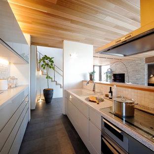 他の地域の広いモダンスタイルのおしゃれなキッチン (一体型シンク、フラットパネル扉のキャビネット、白いキャビネット、御影石カウンター、ベージュキッチンパネル、グレーの床、白いキッチンカウンター) の写真