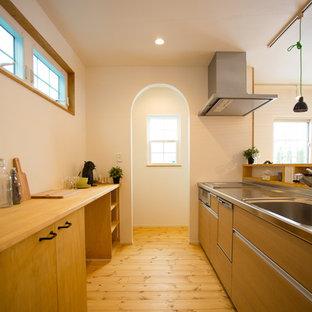 他の地域のアジアンスタイルのおしゃれなキッチン (一体型シンク、フラットパネル扉のキャビネット、中間色木目調キャビネット、ステンレスカウンター、無垢フローリング、茶色い床、茶色いキッチンカウンター) の写真