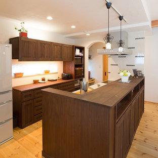 他の地域のアジアンスタイルのおしゃれなキッチン (一体型シンク、落し込みパネル扉のキャビネット、濃色木目調キャビネット、木材カウンター、白いキッチンパネル、無垢フローリング、茶色い床) の写真
