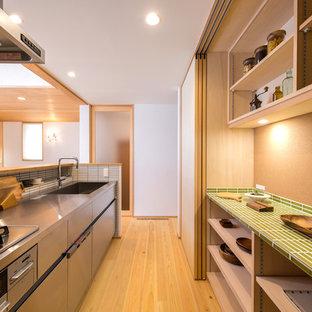 横浜のアジアンスタイルのおしゃれなキッチン (シングルシンク、オープンシェルフ、淡色木目調キャビネット、ステンレスカウンター、白いキッチンパネル、セラミックタイルのキッチンパネル、淡色無垢フローリング、茶色い床) の写真