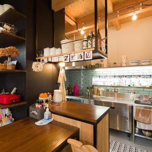 他の地域のインダストリアルスタイルのおしゃれなキッチン (アンダーカウンターシンク、オープンシェルフ、ステンレスカウンター、緑のキッチンパネル、サブウェイタイルのキッチンパネル、シルバーの調理設備の、コンクリートの床) の写真