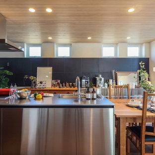 他の地域のモダンスタイルのおしゃれなキッチン (フラットパネル扉のキャビネット、ステンレスカウンター、茶色い床) の写真