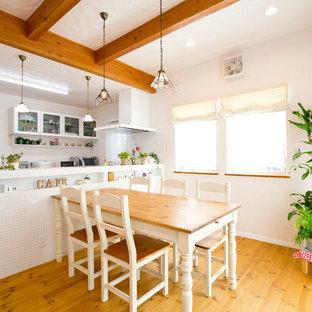 他の地域の地中海スタイルのおしゃれなキッチン (アンダーカウンターシンク、人工大理石カウンター、パネルと同色の調理設備、テラコッタタイルの床、茶色い床) の写真