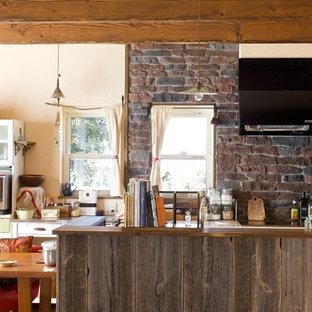 他の地域のアジアンスタイルのおしゃれなキッチン (シングルシンク、濃色無垢フローリング、茶色いキッチンパネル、レンガのキッチンパネル、黒い調理設備) の写真