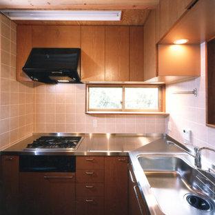 Geschlossene, Kleine Asiatische Küche in L-Form mit integriertem Waschbecken, Kassettenfronten, hellbraunen Holzschränken, Edelstahl-Arbeitsplatte, Rückwand aus Keramikfliesen, schwarzen Elektrogeräten, braunem Holzboden, braunem Boden und Küchenrückwand in Rosa in Tokio