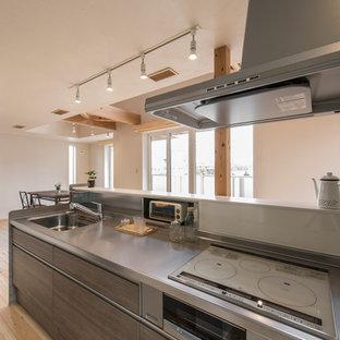 東京都下のカントリー風おしゃれなキッチン (シングルシンク、フラットパネル扉のキャビネット、茶色いキャビネット、ステンレスカウンター、淡色無垢フローリング、ベージュの床) の写真
