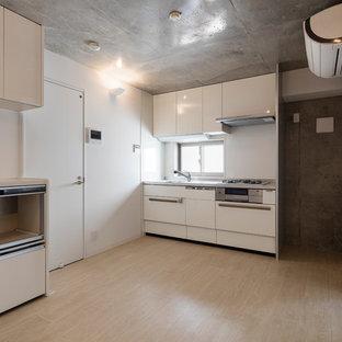 東京23区の中サイズのモダンスタイルのおしゃれなキッチン (シングルシンク、フラットパネル扉のキャビネット、白いキャビネット、ステンレスカウンター、白いキッチンパネル、ガラス板のキッチンパネル、シルバーの調理設備の、クッションフロア、アイランドなし、ピンクの床、グレーのキッチンカウンター) の写真