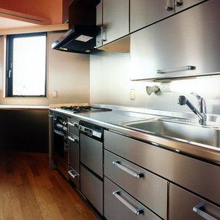 Idee per una cucina minimalista di medie dimensioni con lavello a vasca singola, ante lisce, ante in acciaio inossidabile, top in granito, paraspruzzi grigio, paraspruzzi con lastra di vetro, elettrodomestici colorati, pavimento in compensato, isola, pavimento marrone e top arancione