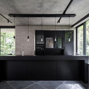 東京23区の中くらいのコンテンポラリースタイルのおしゃれなキッチン (フラットパネル扉のキャビネット、グレーのキャビネット、パネルと同色の調理設備、グレーの床、黒いキッチンカウンター) の写真