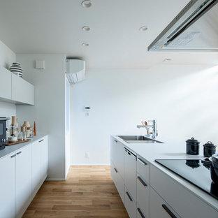 東京23区のモダンスタイルのおしゃれなキッチン (アンダーカウンターシンク、インセット扉のキャビネット、白いキャビネット、白いキッチンパネル、シルバーの調理設備、無垢フローリング、ベージュの床、白いキッチンカウンター) の写真