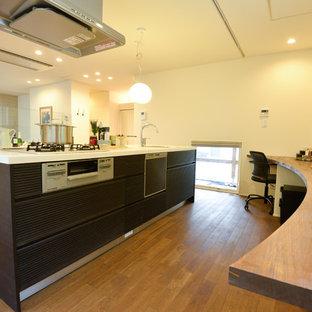 他の地域のモダンスタイルのおしゃれなキッチン (シングルシンク、ルーバー扉のキャビネット、濃色木目調キャビネット、無垢フローリング、茶色い床、茶色いキッチンカウンター) の写真
