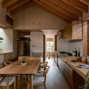 他の地域のアジアンスタイルのおしゃれなキッチン (シングルシンク、フラットパネル扉のキャビネット、中間色木目調キャビネット、ステンレスカウンター、白いキッチンパネル、濃色無垢フローリング、茶色い床) の写真