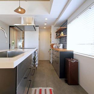 東京23区のインダストリアルスタイルのおしゃれなキッチン (ドロップインシンク、フラットパネル扉のキャビネット、グレーのキャビネット、青いキッチンパネル、グレーの床、白いキッチンカウンター) の写真