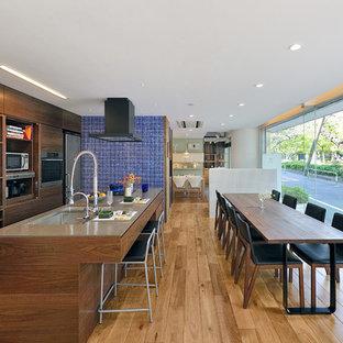 Modern inredning av ett linjärt kök och matrum, med en dubbel diskho, släta luckor, skåp i mellenmörkt trä, bänkskiva i glas, rostfria vitvaror, ljust trägolv och en köksö