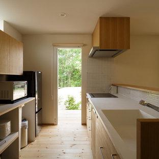 Exempel på ett asiatiskt linjärt kök, med en integrerad diskho, släta luckor, skåp i ljust trä, vitt stänkskydd, stänkskydd i mosaik, rostfria vitvaror, ljust trägolv och en halv köksö