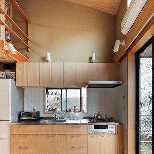 Foto de cocina lineal, de estilo zen, pequeña, abierta, con fregadero de un seno, armarios con paneles lisos, puertas de armario de madera clara, salpicadero verde, suelo de madera clara y suelo marrón