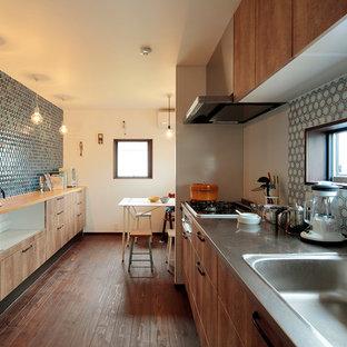 他の地域の中くらいのミッドセンチュリースタイルのおしゃれなキッチン (アンダーカウンターシンク、インセット扉のキャビネット、中間色木目調キャビネット、ステンレスカウンター、ベージュキッチンパネル、モザイクタイルのキッチンパネル、パネルと同色の調理設備、濃色無垢フローリング、アイランドなし、茶色い床、茶色いキッチンカウンター) の写真