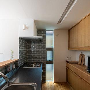 他の地域のアジアンスタイルのおしゃれなキッチン (一体型シンク、インセット扉のキャビネット、中間色木目調キャビネット、ステンレスカウンター、グレーのキッチンパネル、サブウェイタイルのキッチンパネル、パネルと同色の調理設備、無垢フローリング、茶色い床、茶色いキッチンカウンター) の写真