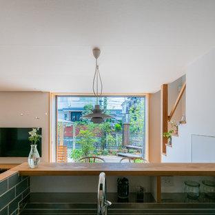 他の地域のアジアンスタイルのおしゃれなI型キッチン (一体型シンク、インセット扉のキャビネット、中間色木目調キャビネット、ステンレスカウンター、グレーのキッチンパネル、サブウェイタイルのキッチンパネル、パネルと同色の調理設備、無垢フローリング、茶色い床、茶色いキッチンカウンター) の写真