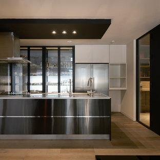 他の地域のモダンスタイルのおしゃれなキッチン (シングルシンク、フラットパネル扉のキャビネット、黒いキャビネット、淡色無垢フローリング、茶色い床) の写真