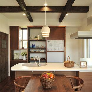 他の地域のアジアンスタイルのおしゃれなキッチン (一体型シンク、フラットパネル扉のキャビネット、中間色木目調キャビネット、白いキッチンパネル、濃色無垢フローリング、茶色い床) の写真