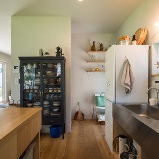 横浜のII型ビーチスタイルのキッチンの画像 (一体型シンク、ステンレスカウンター、シルバーの調理設備、無垢フローリング)