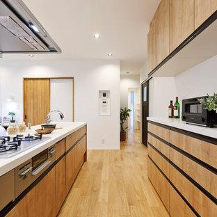 他の地域のコンテンポラリースタイルのおしゃれなII型キッチン (中間色木目調キャビネット、無垢フローリング、茶色い床、白いキッチンカウンター) の写真
