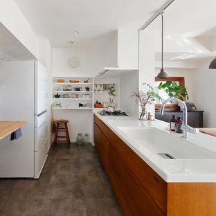 他の地域のアジアンスタイルのおしゃれなキッチン (一体型シンク、フラットパネル扉のキャビネット、中間色木目調キャビネット、グレーの床) の写真