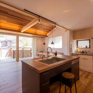 他の地域のアジアンスタイルのおしゃれなキッチン (シングルシンク、フラットパネル扉のキャビネット、淡色木目調キャビネット、木材カウンター、白いキッチンパネル、セメントタイルのキッチンパネル、無垢フローリング、茶色い床、茶色いキッチンカウンター) の写真