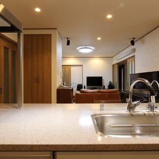 他の地域の中くらいの和風のおしゃれなキッチン (人工大理石カウンター、白いキッチンパネル、合板フローリング、茶色い床、ベージュのキッチンカウンター) の写真