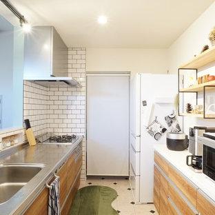 他の地域の北欧スタイルのおしゃれなキッチン (シングルシンク、フラットパネル扉のキャビネット、中間色木目調キャビネット、ステンレスカウンター、白いキッチンパネル、サブウェイタイルのキッチンパネル、マルチカラーの床、白いキッチンカウンター) の写真