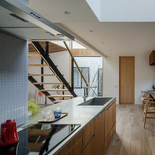 他の地域の北欧スタイルのおしゃれなキッチン (一体型シンク、フラットパネル扉のキャビネット、中間色木目調キャビネット、ステンレスカウンター、無垢フローリング、茶色い床) の写真