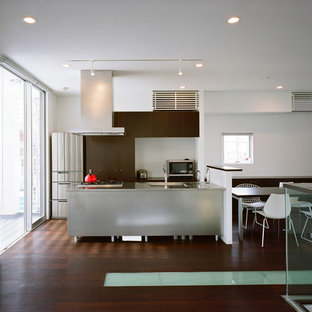 大阪のコンテンポラリースタイルのおしゃれなキッチン (シングルシンク、フラットパネル扉のキャビネット、濃色木目調キャビネット、ステンレスカウンター、濃色無垢フローリング、茶色い床) の写真