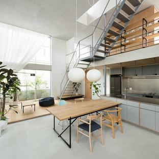 東京23区のコンテンポラリースタイルのおしゃれなキッチン (フラットパネル扉のキャビネット、グレーのキャビネット、ステンレスカウンター、グレーのキッチンパネル、グレーの床、コンクリートの床) の写真