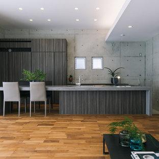 他の地域のアジアンスタイルのおしゃれなキッチン (アンダーカウンターシンク、フラットパネル扉のキャビネット、濃色木目調キャビネット、コンクリートカウンター、グレーのキッチンパネル、パネルと同色の調理設備、無垢フローリング、茶色い床、グレーのキッチンカウンター) の写真
