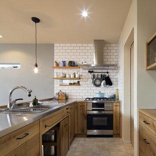 他の地域の北欧スタイルのおしゃれなキッチン (シングルシンク、フラットパネル扉のキャビネット、ヴィンテージ仕上げキャビネット、ステンレスカウンター、ベージュの床、茶色いキッチンカウンター) の写真