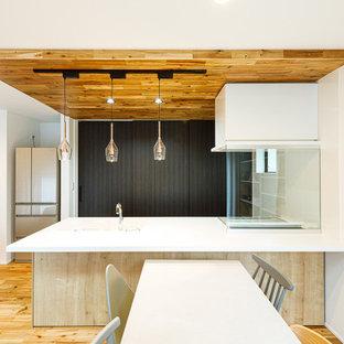 東京都下の中くらいのアジアンスタイルのおしゃれなキッチン (一体型シンク、フラットパネル扉のキャビネット、中間色木目調キャビネット、人工大理石カウンター、白いキッチンパネル、ガラスまたは窓のキッチンパネル、無垢フローリング、茶色い床、白いキッチンカウンター) の写真