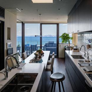 他の地域のビーチスタイルのおしゃれなキッチン (アンダーカウンターシンク、フラットパネル扉のキャビネット、黒いキャビネット、白いキッチンパネル、黒い調理設備、濃色無垢フローリング) の写真