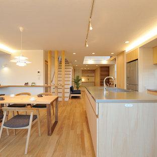 他の地域の北欧スタイルのおしゃれなキッチン (一体型シンク、フラットパネル扉のキャビネット、淡色木目調キャビネット、ステンレスカウンター、白いキッチンパネル、淡色無垢フローリング、茶色い床、ベージュのキッチンカウンター) の写真