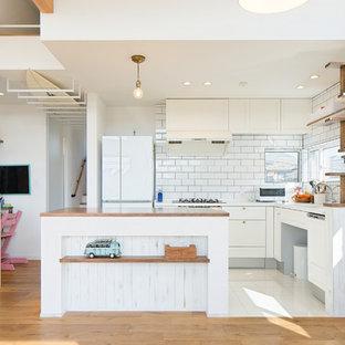 他の地域のビーチスタイルのおしゃれなキッチン (落し込みパネル扉のキャビネット、白いキャビネット、白いキッチンパネル、サブウェイタイルのキッチンパネル、白い調理設備、白い床、白いキッチンカウンター) の写真