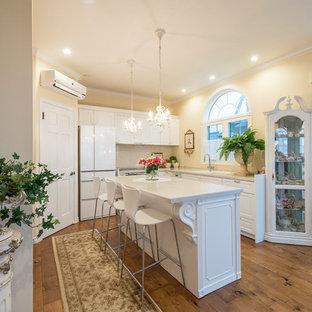 他の地域のヴィクトリアン調のおしゃれなキッチン (ドロップインシンク、落し込みパネル扉のキャビネット、白いキャビネット、ベージュキッチンパネル、無垢フローリング、茶色い床、白いキッチンカウンター) の写真
