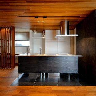 他の地域のコンテンポラリースタイルのおしゃれなキッチン (一体型シンク、フラットパネル扉のキャビネット、白いキャビネット、ステンレスカウンター、黒い床、グレーのキッチンカウンター) の写真