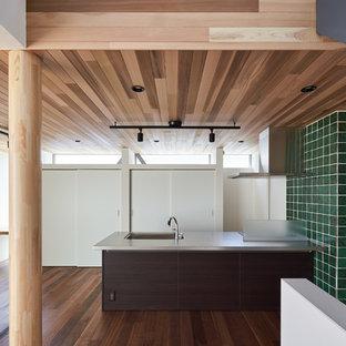 東京23区のコンテンポラリースタイルのおしゃれなキッチン (アンダーカウンターシンク、フラットパネル扉のキャビネット、濃色木目調キャビネット、緑のキッチンパネル、無垢フローリング、茶色い床、グレーのキッチンカウンター) の写真