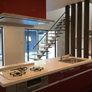 Modern single-wall open plan kitchen in Other with a submerged sink, red cabinets, composite countertops, plywood flooring, an island, brown floors and white worktops.
